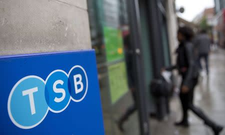 A woman wlalks into a branch of TSB bank in London