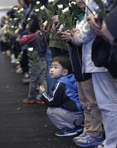 A boy waits to pay tribute to the victims of the sunken ferry Sewol at a group memorial altar in Ansan, South Korea, Saturday, May 3, 2014. More than 300 people are dead or missing in the disaster that has caused widespread grief, anger and shame. (AP Photo/Ahn Young-joon)