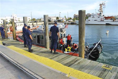 United States Coast Guard officers arrive at their base with a Cuban man they rescued in Key West