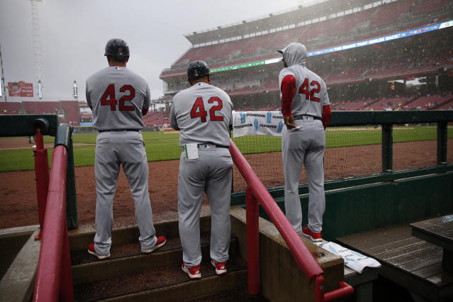 St. Louis Cardinals players and coaches wear No. 42, in honor of Jackie Robinson Day, as they watch the first inning of a baseball game against the Cincinnati Reds, Sunday, April 15, 2018, in Cincinnati. (AP Photo/Gary Landers)
