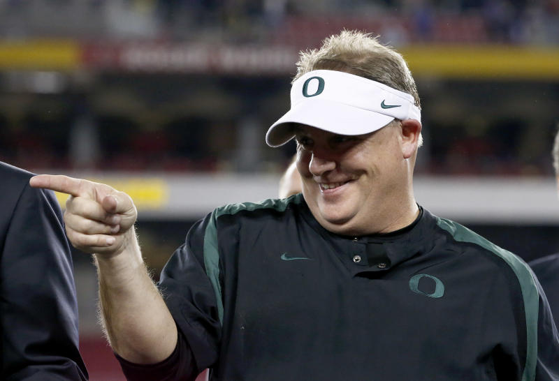 FILE - In this Jan. 3, 2013 file photo, Oregon head coach Chip Kelly celebrates with his players after the Fiesta Bowl NCAA college football game against Kansas State, in Glendale, Ariz. The Philadelphia Eagles have hired Kelly after he originally chose to stay at Oregon. Kelly becomes the 21st coach in team history and replaces Andy Reid, who was fired on Dec. 31 after a 4-12 season. (AP Photo/Ross D. Franklin, FIle)