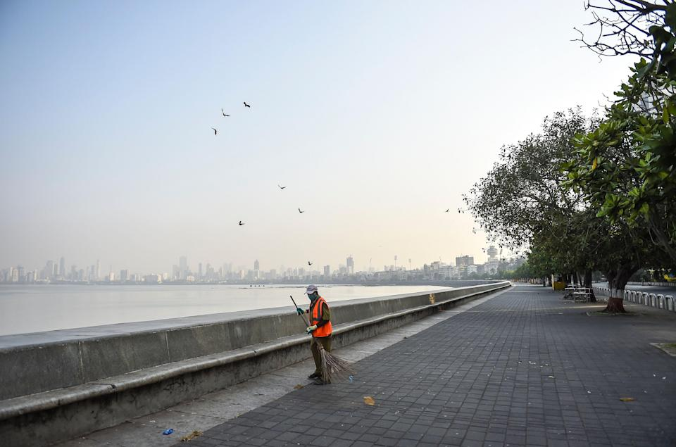 Mumbai: A municipal worker in Mumbai on Thursday, 15 April, cleans a deserted area near the sea front at Marine Drive during restrictions imposed by the state government amid rising COVID-19 coronavirus cases.