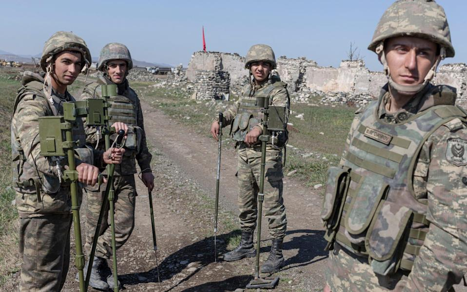 Azerbaijani sappers take a break after sweeping a field of mines near the construction site of new airport in the destroyed town of Fuzuli - Sam Tarling/The Telegraph
