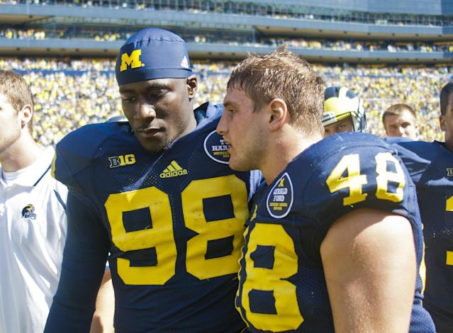 Michigan quarterback Devin Gardner (98) has words with linebacker Desmond Morgan (48) after an NCAA college football game against Akrain in Ann Arbor, Mich., Saturday, Sept. 14, 2013. Michigan won 28-24. Gardner had 3 interceptions and 1 lost fumble. (AP Photo/Tony Ding)