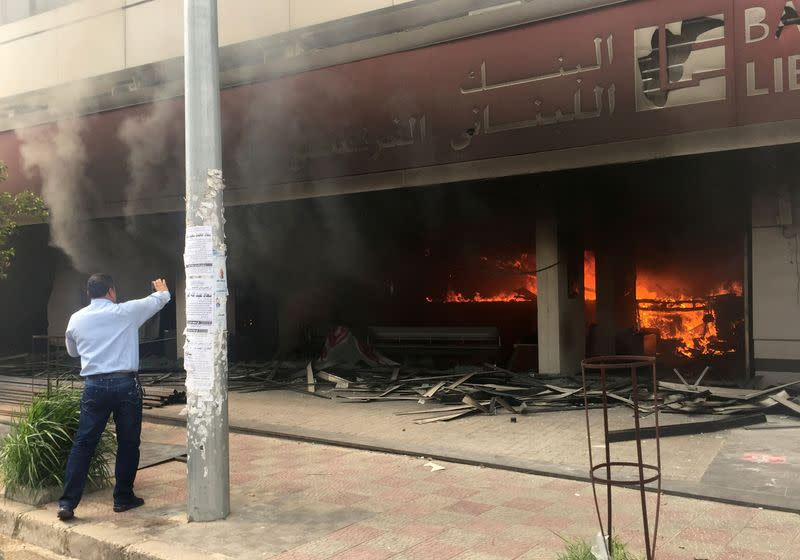 Man takes a picture with his mobile phone of a bank on fire during unrest in Tripoli