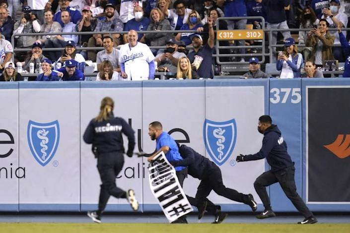 A fan who made his way on to the field is tackled by security personnel during a Diamondbacks Dodgers game