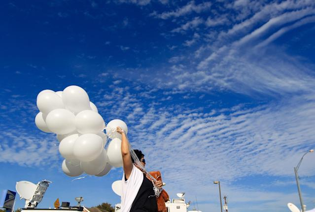 <p>Michelle Trigo, who now lives in San Antonio but grew up in the Sutherland Springs area, carries balloons to lay near the site of Sunday's shooting at the First Baptist Church of Sutherland Springs, Texas, Monday, Nov. 6, 2017. (Photo: Mark Mulligan/Houston Chronicle via AP) </p>