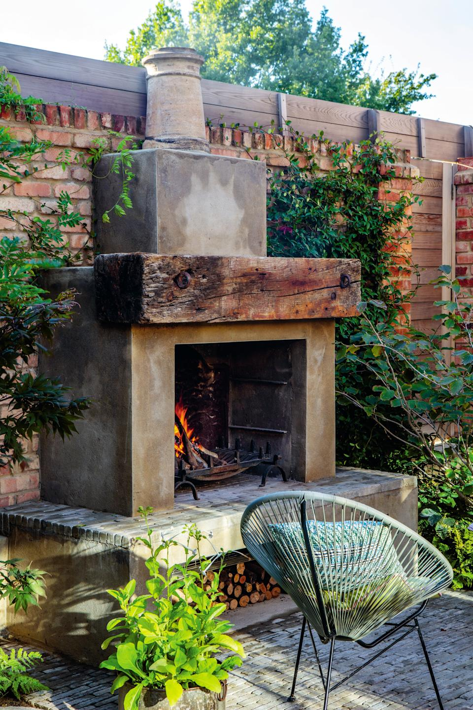 Outdoor hosting: in front of a coral pink outdoor fireplace designed by Krempell are two lightweight Acapulco-style chairsClive Nichols