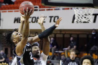 Kansas State guard Selton Miguel (2) goes to the basket in front of Oklahoma State forward Matthew-Alexander Moncrieffe, right, in the first half of an NCAA college basketball game Saturday, Feb. 13, 2021, in Stillwater, Okla. (AP Photo/Sue Ogrocki)
