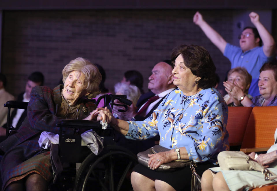 Aranka Engel, 103, left, holds the hand of fellow Holocaust survivor Jean Kurz, 81, while watching Orthodox Jewish singer Yaakov Shwekey perform at a concert honoring them and dozens of other Holocaust survivors on Monday, June 14, 2021, at the Yeshivah of Flatbush theater at Joel Braverman High School in the Brooklyn borough of New York. It was the first large gathering for New York-area Holocaust survivors after more than a year of isolation due to the coronavirus pandemic. (AP Photo/Jessie Wardarski)