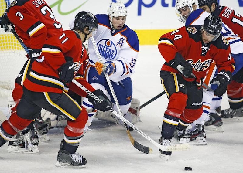 Edmonton Oilers' Ryan Smyth, center, digs for the puck with Calgary Flames' Mikael Backlund, left, from Sweden, and Chris Butler during the first period of an NHL hockey game Saturday, Nov. 16, 2013 in Calgary, Alberta. (AP Photo/The Canadian Press, Jeff McIntosh)