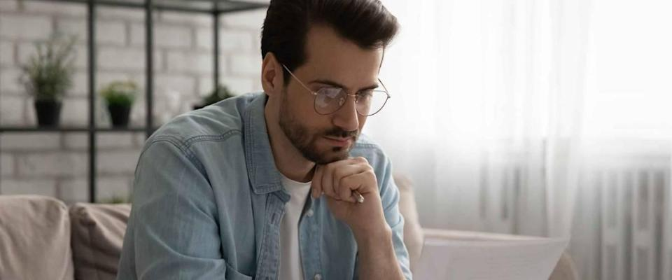 Thoughtful young caucasian man in glasses sit on sofa in living room read postal letter