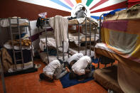 Asylum-seekers pray next to their beds at the Modern Christian Mission Church in Fuerteventura, one of the Canary Islands, Spain, on Saturday, Aug. 22, 2020. The Modern Christian Mission is the main shelter for rescued migrants on the island of Fuerteventura. (AP Photo/Emilio Morenatti)