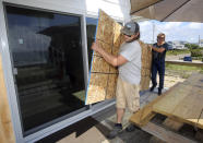 James Masog, center, and Gary Tavares, right, move particle board into place to board up the sliding glass doors of a clients house in Charlestown, R.I., ahead of Hurricane Henri, Saturday, Aug. 21, 2021. New Englanders, bracing for their first direct hit by a hurricane in 30 years, are taking precautions as Tropical Storm Henri barrels toward the southern New England coast. (AP Photo/Stew Milne)