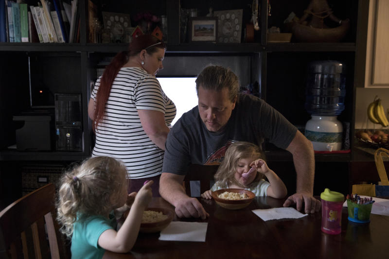 In this Wednesday, Sept. 5, 2018, photo, middle-school English teacher Maryam Powers, background left, works on her computer as her boyfriend, Jean-Paul Varagnat, chats with their two daughters around the dinner table in Salinas, Calif. Powers rents out the master bedroom for $800 a month to afford the mortgage on the three-bedroom home she purchased in 2015. (AP Photo/Jae C. Hong)