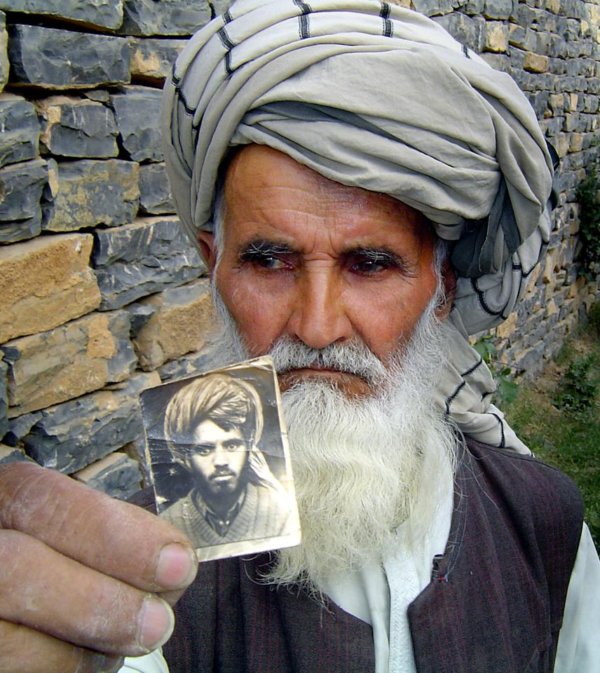 """Bakhtar Gul, the father of Khiali Gul who is currently incarcerated at Guantanamo Bay, holds a photograph of him at his home in Yaqubi, about 140 kilometres (87 miles) south east of Kabul on May 13, 2004. Human Rights Watch has catalogued mistreatment of Afghan detainees it describes as """"systematic"""" and is demanding that the results of an inquiry into two deaths be released. Photograph taken on May 13, 2004. REUTERS/Stringer  TBW"""