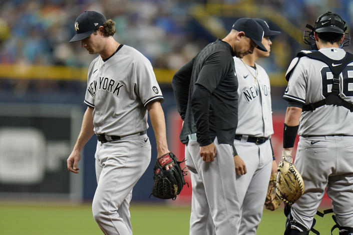 New York Yankees starting pitcher Gerrit Cole, left, reacts after being taken out of the game against the Tampa Bay Rays by manager Aaron Boone, center, during the sixth inning of a baseball game Thursday, July 29, 2021, in St. Petersburg, Fla. (AP Photo/Chris O'Meara)