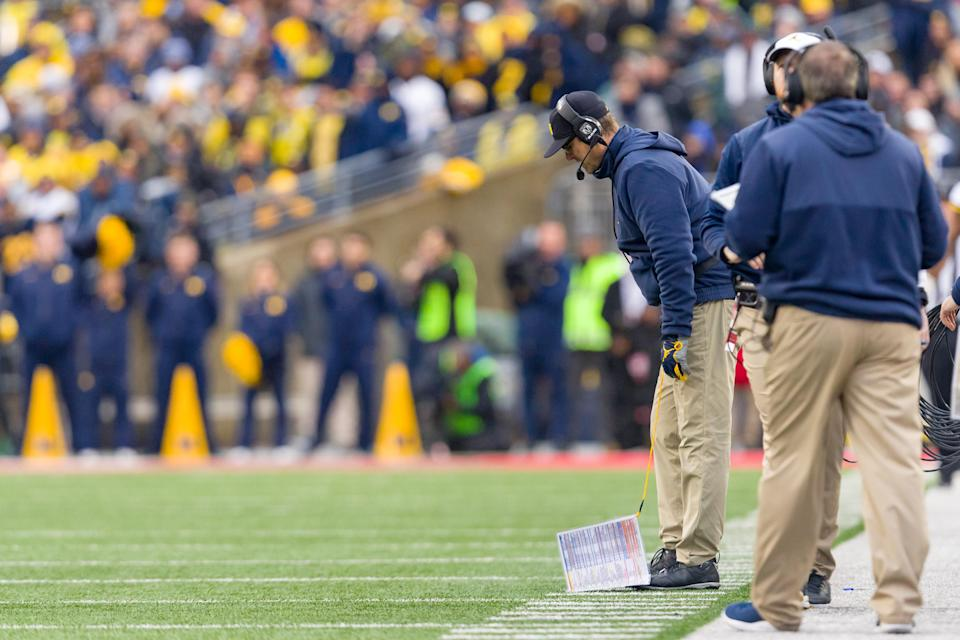 Michigan Wolverines head coach Jim Harbaugh drops his play card during his team's loss to the Ohio State Buckeyes on Saturday. (Getty)