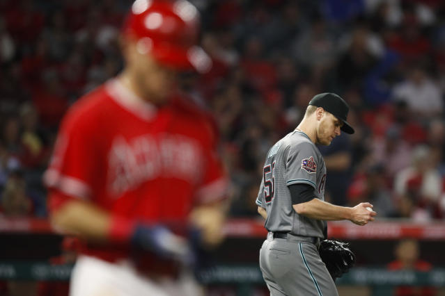 Arizona Diamondbacks starting pitcher Matt Koch, right, looks at the ball after hitting Los Angeles Angels' Ian Kinsler with a pitch during the fifth inning of a baseball game Tuesday, June 19, 2018, in Anaheim, Calif. (AP Photo/Jae C. Hong)