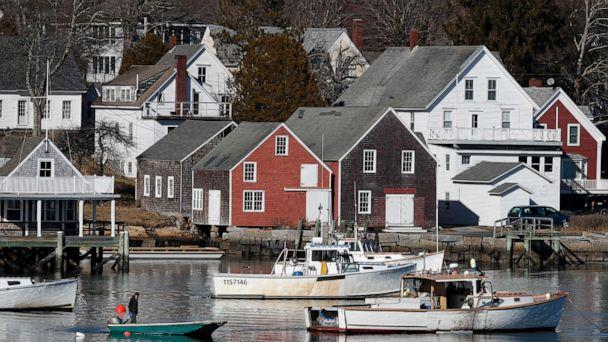 PHOTO: A boater motors past lobster boats moored off North Haven, Maine, Monday, March 16, 2020. (Robert F. Bukaty/AP)
