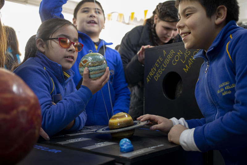 Blind school children take part in a sensorial experience with tools created by NASA and Edinburgh University to experience an eclipse, during an event in the Helen Keller school in Santiago, Chile, Tuesday, June 25, 2019. The event comes exactly one week ahead of a total solar eclipse which is set to be fully visible in various South American countries, including Chile. (AP Photo/Esteban Felix)