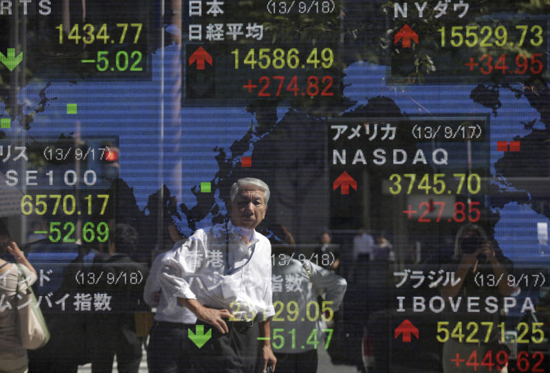 A man is reflected on the electronic stock board of a securities firm in Tokyo, Wednesday, Sept. 18, 2013. Asian stock markets struggled to find their footing Wednesday as traders hesitated to make bold moves before the Federal Reserve winds up a crucial policy meeting later in the day. (AP Photo/Shizuo Kambayashi)