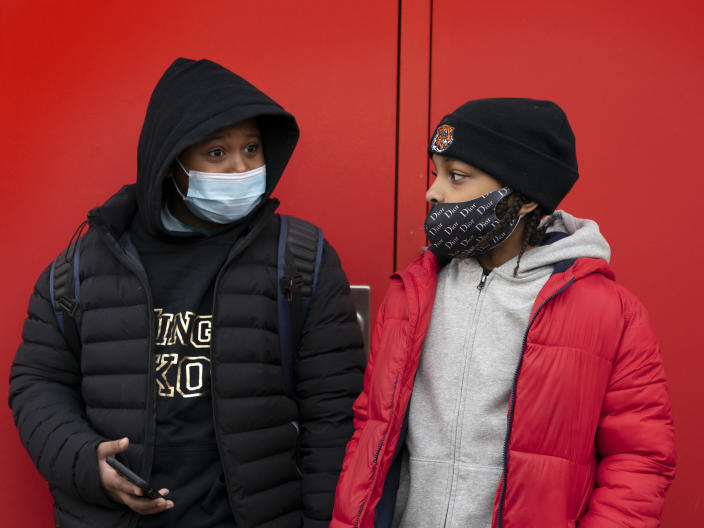 Students wait for the doors to open at P.S. 134 Henrietta Szold Elementary School, Monday, Dec. 7, 2020, in New York. Public schools reopened for in-school learning Monday after being closed since mid-November. (AP Photo/Mark Lennihan)