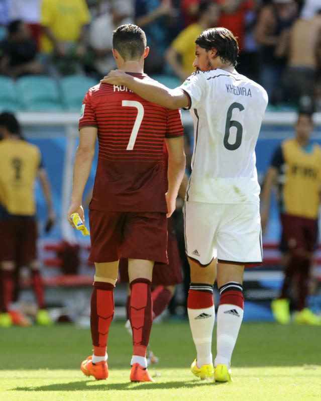 Portugal's Cristiano Ronaldo (7) walks off the pitch with Germany's Sami Khedira (6) at the half during the group G World Cup soccer match between Germany and Portugal at the Arena Fonte Nova in Salvador, Brazil, Monday, June 16, 2014. (AP Photo/Paulo Duarte)
