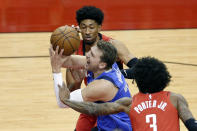 Dallas Mavericks guard Luka Doncic (77) is fouled as he drives to the basket between during the first half of an NBA basketball game Wednesday, April 7, 2021, in Houston. (AP Photo/Michael Wyke, Pool)