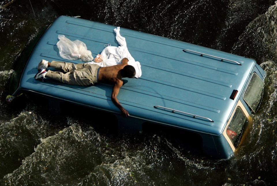 <p>2005. Reuters Caption: A man clings to the top of a vehicle before being rescued by the U.S. Coast Guard from the flooded streets of New Orleans, in the aftermath of Hurricane Katrina.</p>