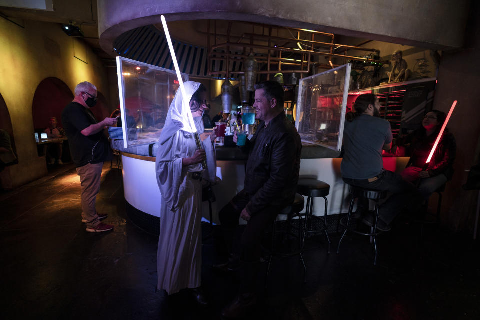 Elen Monocroussos, left, and boyfriend, James Stevens, are dressed in Star Wars costumes as they celebrate Star Wars Day at Scum and Villainy Cantina, a geek bar located on Hollywood Blvd, in Los Angeles, Tuesday, May 4, 2021. California has the lowest infection rate in the country. Los Angeles County, which is home to a quarter of the state's nearly 40 million people and has endured a disproportionate number of the state's 60,000 deaths, didn't record a single COVID-19 death Sunday or Monday, which was likely due to incomplete weekend reporting but still noteworthy. (AP Photo/Jae C. Hong)