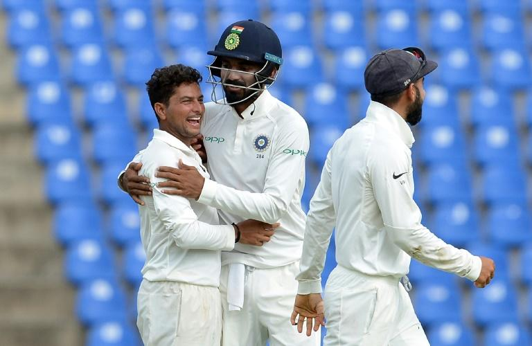 India's Kuldeep Yadav (L) celebrates with teammates after dismissing Sri Lanka's Dilruwan Perera on the second day of the third Test at the Pallekele International Cricket Stadium in Pallekele on August 13, 2017