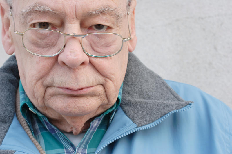 We see a close-up of an older man looking very displeased.