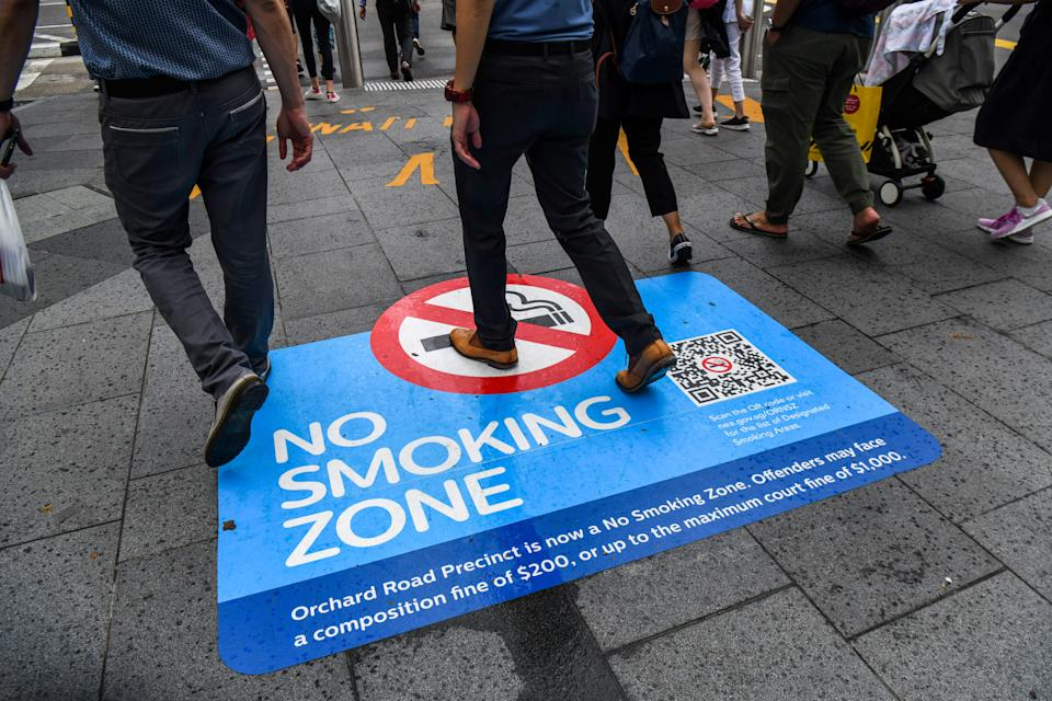 People walk past a 'No Smoking Zone' sign on a walkway along Orchard Road in Singapore on 1 April, 2019. (AFP file photo)