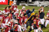 Wisconsin players celebrate with the Paul Bunyan Axe after they defeated Minnesota in overtime of an NCAA college football game Saturday, Dec. 19, 2020, in Madison, Wis. (AP Photo/Andy Manis)