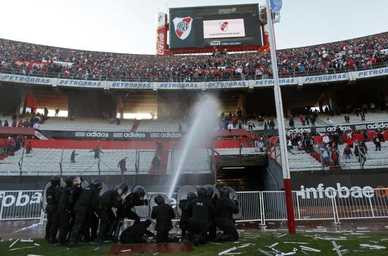 Police spray water at River Plate soccer fans to keep them from jumping over the gate and on to the field at the end of an Argentine promotion soccer game with Belgrano in Buenos Aires, Argentina, Sunday June 26, 2011. Legendary club River Plate has been relegated to the Argentine second division for the first time in its 110-year history, going down Sunday after a 1-1 draw with Belgrano in the second leg of a demotion playoff.  (AP Photo/Ricardo Mazalan)