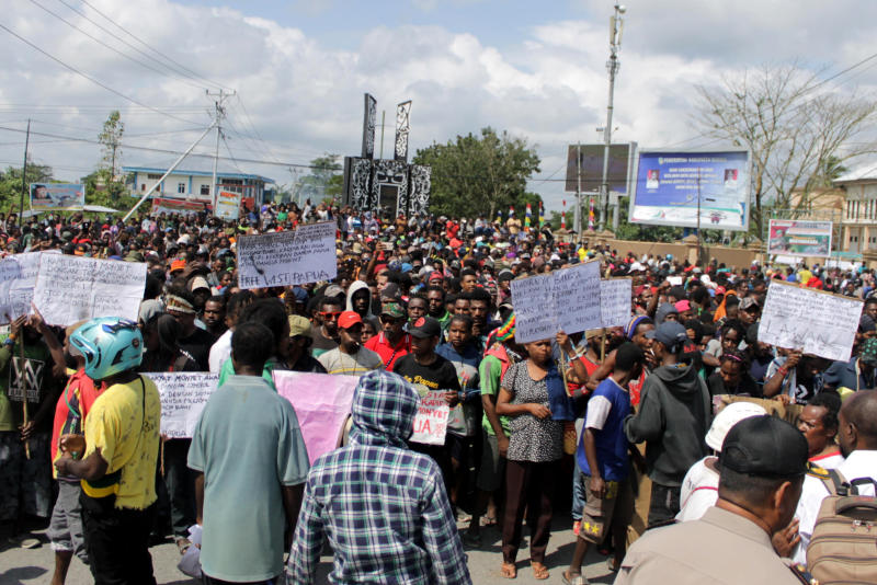 Papuans hold posters during a protest in Timika, Papua province, Wednesday, Aug. 21, 2019. Indonesia has deployed over 1,000 security personnel to the restive province of West Papua amid spreading violent protests sparked by accusations that security forces had arrested and insulted Papuan students in East Java . (AP Photo/Jimmy Rahadat)