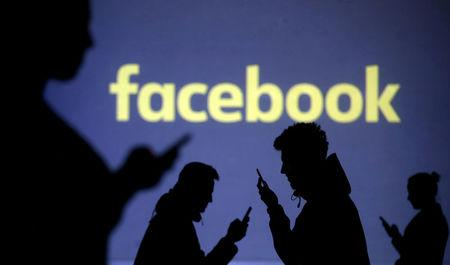 FILE PHOTO: Silhouettes of mobile users are seen next to a screen projection of Facebook logo