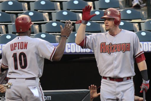 Arizona Diamondbacks' Justin Upton (10) is congratulated by Chris Johnson, right, after scoring on a double by Paul Goldschmidt during the first inning of a baseball game Friday, Sept. 21, 2012 in Denver. (AP Photo/Barry Gutierrez)