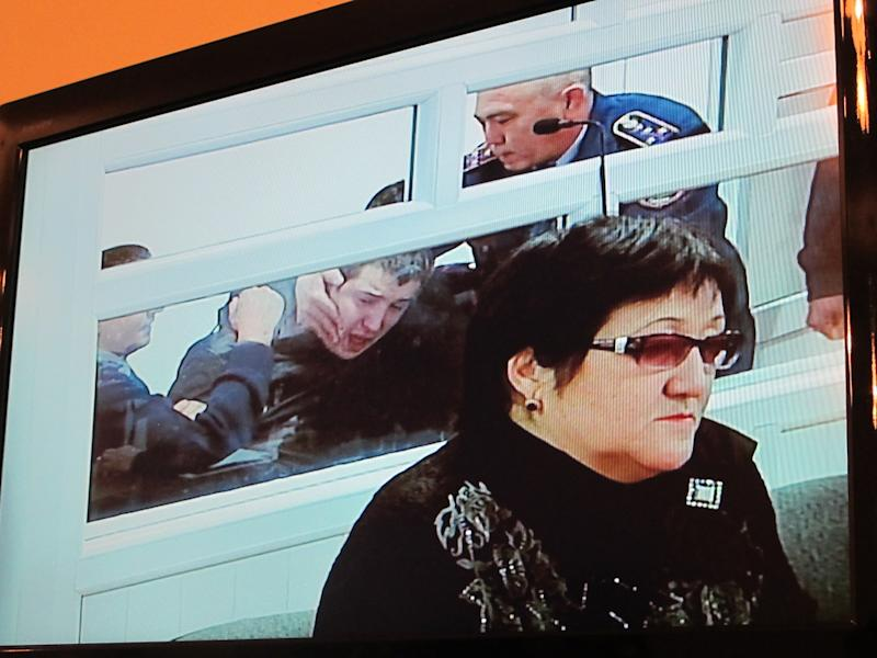 This photo taken of a relayed televised image from a courtroom shows defense lawyer Zhumagaysha Sarzhanova sitting in front of Vladislav Chelakh as he struggles with guards Tuesday, Dec. 11, 2012, during the last day of his trial in the southern Kazakhstan city of Taldykorgan. Chelakh, a conscript in Kazakhstan's army, is accused of killing 14 fellow soldiers and a park ranger in a May massacre that shocked the Central Asian nation. (AP Photo/Peter Leonard)