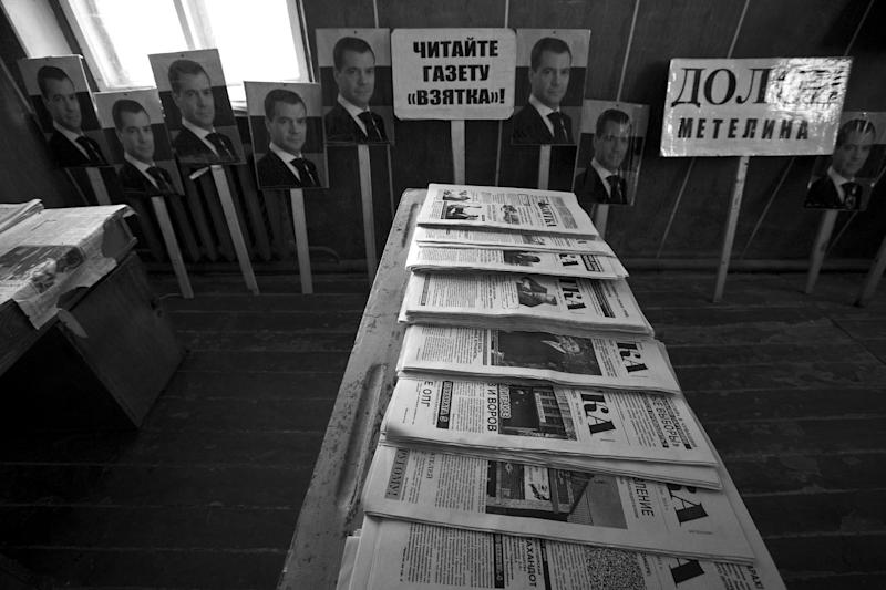 """This Nov. 14, 2012, photo shows the room in an abandoned barn where Eduard Mochalov keeps old copies of The Bribe and posters from protests against corruption in Chuvashia, in Yarabaikasy near Cheboksary, the capital city of Chuvashia, Russia. Posters show portraits of Russian Prime Minister Dmitry Medvedev and says """"Read the newspaper Bribe."""" Eduard Mochalov has found a new lease on life as a crusading journalist investigating corruption in his native region, fueled by tips from disgruntled businessmen and government workers. Undeterred by a system where the law is selectively used to protect the powerful and crack down on critics, Mochalov has quickly earned cult status _ not to mention the ire of countless local officials _ throughout the small province of Chuvashia. (AP Photo/Alexander Zemlianichenko)"""
