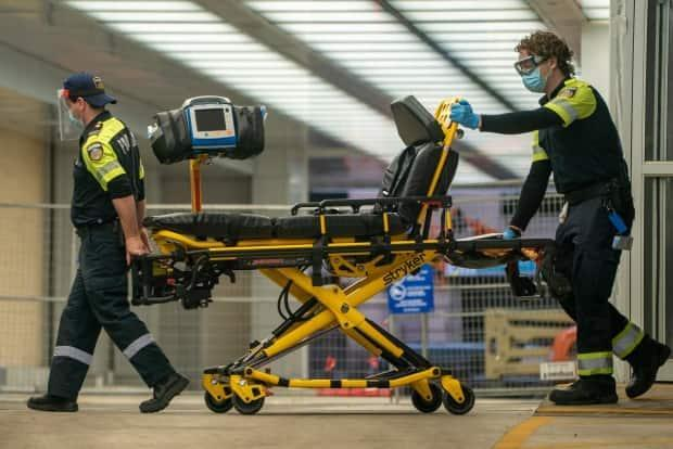 Two paramedics push a gurney out of Mt. Sinai Hospital's emergency entrance in Toronto after dropping off a patient on March 26, 2021. (Sam Nar/CBC - image credit)