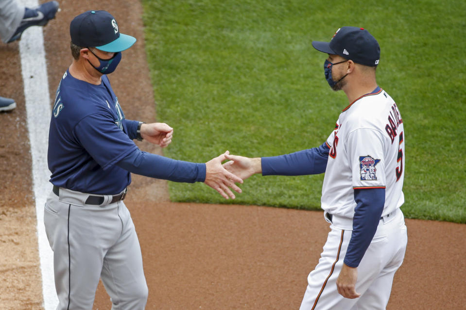 Seattle Mariners manager Scott Servais greets Minnesota Twins manager Rocco Baldelli during the introductions at the home opener baseball game Thursday, April 8, 2021, in Minneapolis. (AP Photo/Bruce Kluckhohn)