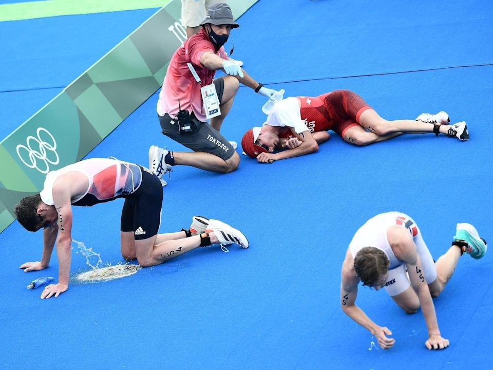 A triathlete pukes while others lay on the ground at the Tokyo Olympics.
