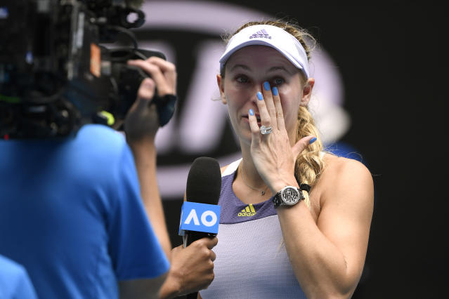Denmark's Caroline Wozniacki wipes away tears after a third round loss to Tunisia's Ons Jabeur at the Australian Open, signaling the end of her pro career. (AP/Andy Brownbill)