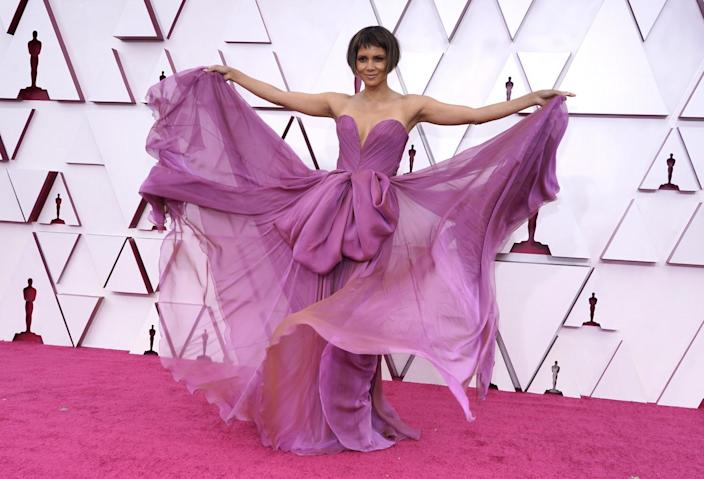 Halle Berry holding out the flowy skirt of her strapless light purple gown