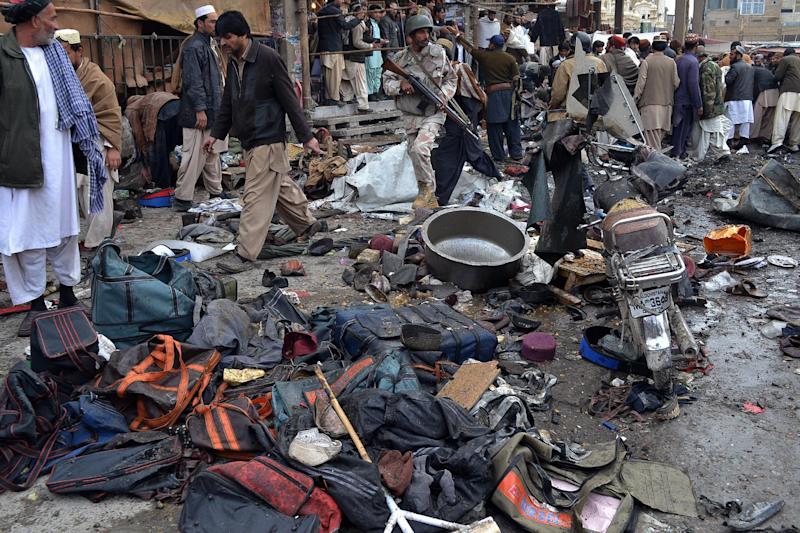 A Pakistani paramilitary soldier and local residents gather at the site of bomb blast in Quetta, Pakistan, Thursday, Jan. 10, 2013. A bomb targeting paramilitary soldiers killed scores of people in southwest Pakistan, officials said. (AP Photo/Arshad Butt)