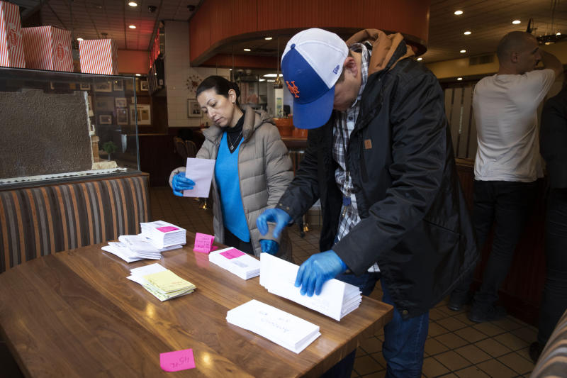Employees of Junior's Restaurant sort paychecks for fellow workers who are picking them up, Thursday, March 19, 2020 in the Brooklyn borough of New York. The restaurant is closed temporarily due to the coronavirus. The company has laid off 650 of 850 employees at its four restaurants. (AP Photo/Mark Lennihan)