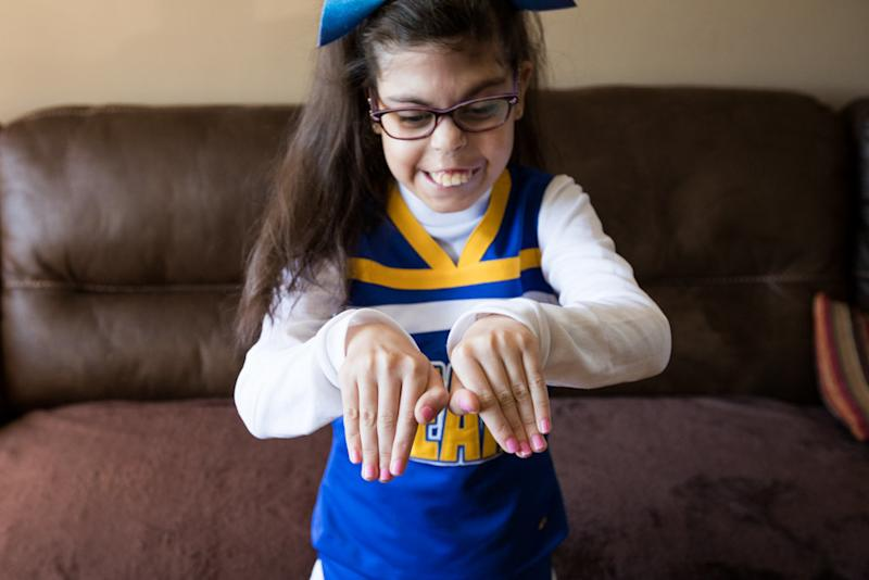 "Gianna was diagnosed with <a href=""https://ghr.nlm.nih.gov/condition/22q112-deletion-syndrome"" target=""_blank"">22q11.2 deletion syndrome</a> in utero. Although she has had 26 surgeries, she is still able to participate in her town's general cheering squad. (Karen Haberberg)"