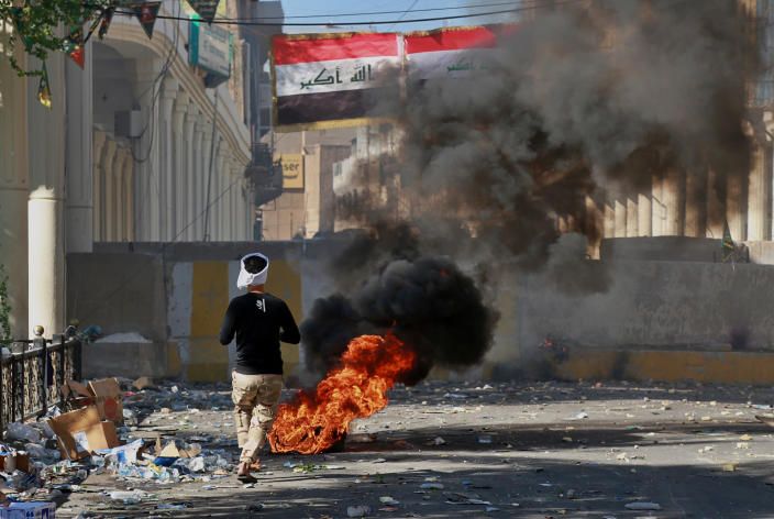 Anti-government protesters set fire during clashes between Iraqi security forces and anti-government protesters in the al-Rasheed street in Baghdad, Iraq, Friday, Nov. 8, 2019. The demonstrators complain of widespread corruption, lack of job opportunities and poor basic services, including regular power cuts despite Iraq's vast oil reserves. They have snubbed limited economic reforms proposed by the government, calling for it to resign. (AP Photo/Khalid Mohammed)